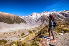 Young man visiting Mount Cook New Zealand. Backpacking person enjoys beautiful natural landscape. Inspirational concept of a. Traveler in breathtaking view royalty free stock photo
