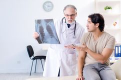 Young man visiting old male doctor radiologist. The young men visiting old male doctor radiologist royalty free stock photography