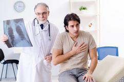 Young man visiting old male doctor radiologist. The young men visiting old male doctor radiologist stock photography