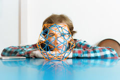 Young Man And The Volumetric Model Of Geometric Solid. Coloured three-dimensional model of geometric solid against the background of the young man`s face Royalty Free Stock Images