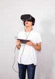 Young Man in VR Glasses. Surprised Young Man in Virtual Reality Glasses by the Wall Royalty Free Stock Images