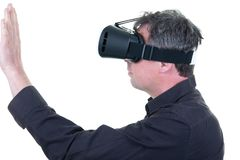 Young man with VR glasses touching imaginary interface indoors stock images
