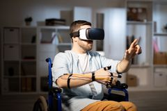 Young man with vr goggle. Modern young man with vr goggle and sensors pointing at object or touching display during virtual experience royalty free stock images
