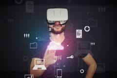 Young man in VR-headset pressing icon on virtual interactive sc Stock Photography