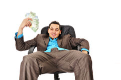 Young man with wad of money. Closeup of smiling young businessman slouching in leather chair with wad of money, isolated on white background Stock Image