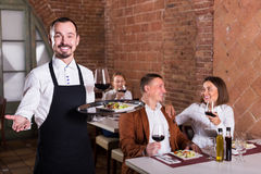 Young man waiter demonstrating country restaurant. Young men waiter demonstrating country restaurant to visitors Royalty Free Stock Image