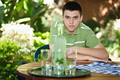 Young man waiting. Young caucasian male waiting at the table, lemonade bottle with mint in front Royalty Free Stock Photography