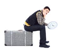 Young man waiting at airport, holding big clock Stock Photo