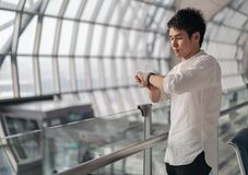 Man waiting for flight and looking smart watch in airport royalty free stock images