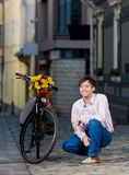 Young man waiting for his date near a bicycle Stock Photo