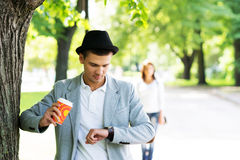 Young man waiting for his love in the park checking the watch Stock Photography