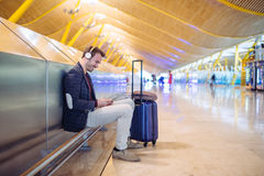 Young man waiting listening music and using mobile phone at the. Airport with a suitcase Royalty Free Stock Images
