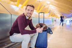 Young man waiting listening music and using mobile phone at the. Airport with a suitcase Royalty Free Stock Photos