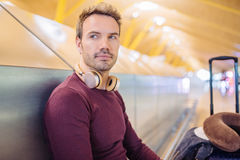 Young man waiting listening music and using mobile phone at the. Airport with a suitcase Stock Image