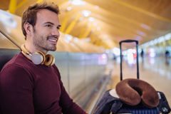 Young man waiting listening music and using mobile phone at the. Airport with a suitcase Royalty Free Stock Image