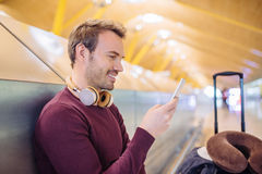 Young man waiting listening music and using mobile phone at the. Airport with a suitcase Stock Photography