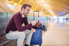 Young man waiting listening music and using mobile phone at the. Airport with a suitcase Stock Photo