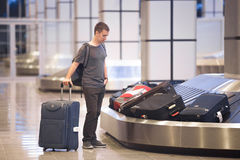 Young man waiting for luggage. Young handsome man passenger in his 20s waiting to pick luggage at baggage conveyor in arrivals lounge of airport terminal Stock Image