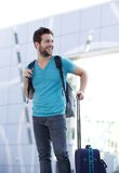 Young man waiting outside with bags. Portrait of a young man waiting outside with bags Royalty Free Stock Photos