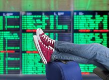 Teenage passenger waiting. Young man waiting for the plane at international airport with the flight information board Royalty Free Stock Images