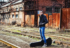 Young man waiting for train among industrial ruins Stock Photography