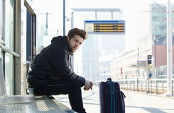 Young man waiting for train with suitcase travel bag Stock Image