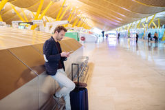 Young man waiting and using mobile phone at the airport.  Stock Image