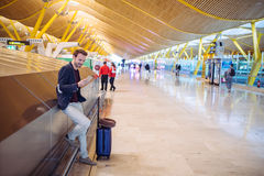 Young man waiting and using mobile phone at the airport.  Royalty Free Stock Images