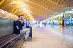 Young man waiting and using mobile phone at the airport.  Royalty Free Stock Photography