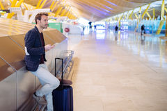 Young man waiting and using mobile phone at the airport.  Royalty Free Stock Photo