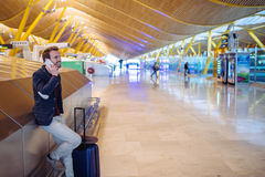 Young man waiting and using mobile phone at the airport.  Stock Photography