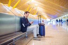 Young man waiting and using mobile phone at the airport.  Royalty Free Stock Photos