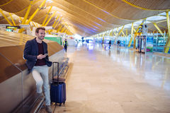 Young man waiting and using mobile phone at the airport.  Stock Photo
