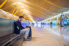 Young man waiting and using mobile phone at the airport.  Royalty Free Stock Image