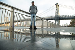 A young man waits along The East River, underneath the Williamsburg Bridge royalty free stock images