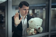 Young man waits for a meeting. Young man looks out the window and waits for a meeting. He has a teddy bear in his hands Stock Image