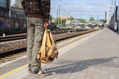 Young man waits train on railway station Stock Photo