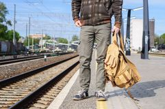 Young man waits train on railway station Stock Image