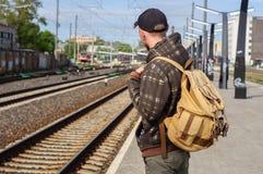 Young man waits train on railway station Stock Photos