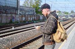 Young man waits train on railway station Royalty Free Stock Image