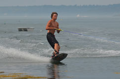 Young Man Wakeboarding in Casco Bay with a Dinghy in the Backgro. Young man wakeboarding off the coast of an island in Maine Stock Photos
