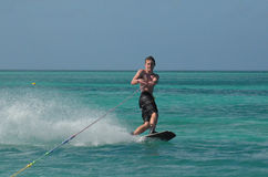 Young Man Wakeboarding on a Perfect Day in Aruba. Young man riding a wakeboard in Aruba Royalty Free Stock Photo