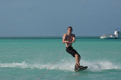 Young Man Wakeboarding in Tropical Warm Waters Off Aruba. Young guy wakeboarding in tropical blue waters off Aruba Stock Photos