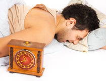 Young man wakes to a loud alarm clock Stock Image