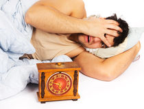 Young man wakes to a loud alarm clock Royalty Free Stock Photo