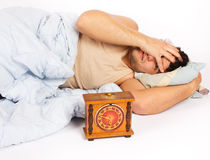 Young man wakes to a loud alarm clock Stock Photos