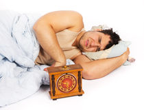 Young man wakes to a loud alarm clock. Angry man and alarm clock in bedroom Stock Photography
