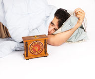 Young man wakes to a loud alarm clock Stock Photo