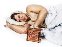 Young man wakes to a loud alarm clock. Angry man and alarm clock in bedroom Royalty Free Stock Image