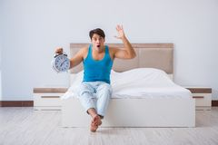 The young man waking up in bed. Young man waking up in bed Royalty Free Stock Photography